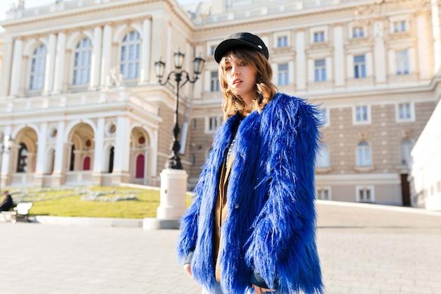 Стильная красивая девушка с кудрявой прической в синей шубе позирует на солнце во время прогулки по городу