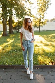 운동화 유행 선글라스에 유행 빈티지 청바지에 흰색 티셔츠에 세련된 예쁜 hipster 젊은 여자는 녹색 나무 사이 공원에서 산책.