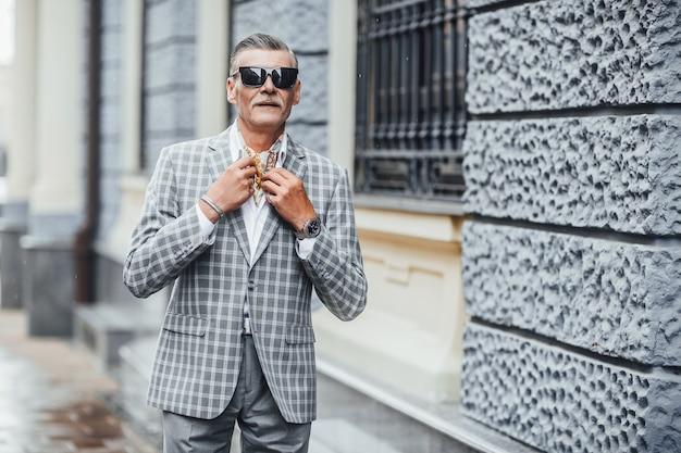 Стильный довольно старший мужчина идет по городу и держит куртку