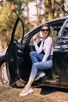 Стильная красивая женщина с красными губами расслабляется, сидя в своей машине на открытом воздухе и глядя на пейзаж
