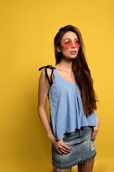 青いtシャツとデニムのスカートと黄色の壁にポーズをとる丸いピンクのメガネを身に着けているスタイリッシュなきれいな女性