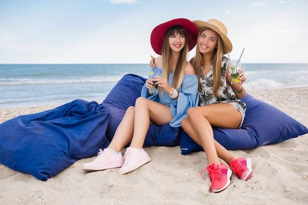 熱帯のビーチで夏休みにスタイリッシュなきれいな女性、友達、ファッショントレンドアクセサリー、笑顔、細い足、砂の上に座って、スニーカーで長い脚を楽しんで