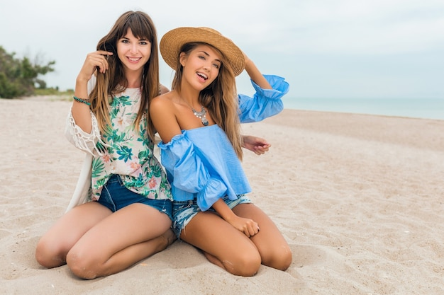 Stylish pretty women on summer vacation on tropical beach, bohemian style, friends travel together