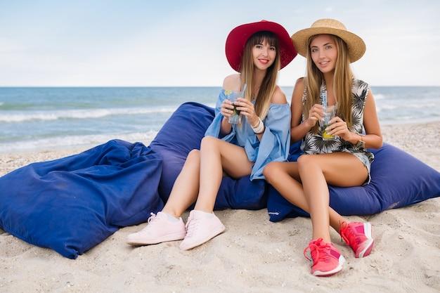 Stylish pretty women on summer vacation on tropical beach