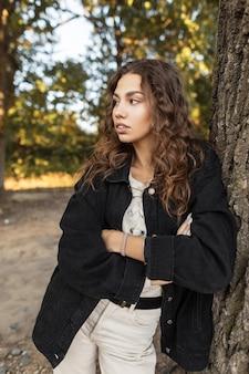 시골의 자연에 쉬고 있는 세련된 블랙 데님 재킷에 곱슬머리를 한 세련된 예쁜 젊은 여성 모델. 여성청바지 스타일과 상큼한 아름다움