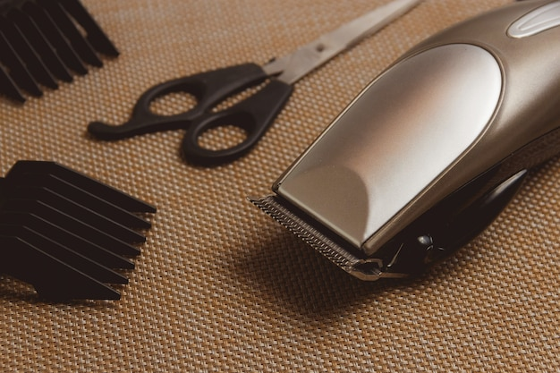 Stylish professional hair clippers, accessories on brown table