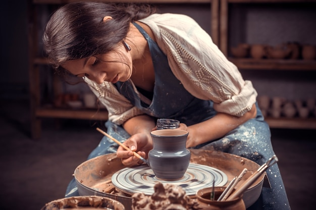 Stylish professional potter making ceramic pottery on wheel