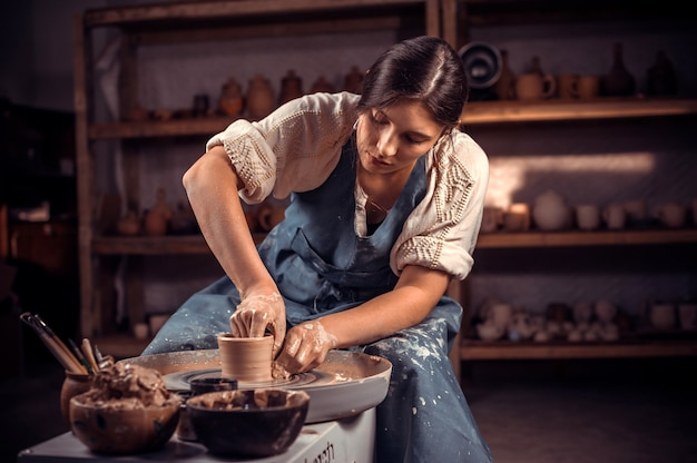 Stylish professional potter making pottery from wet clay on wheel