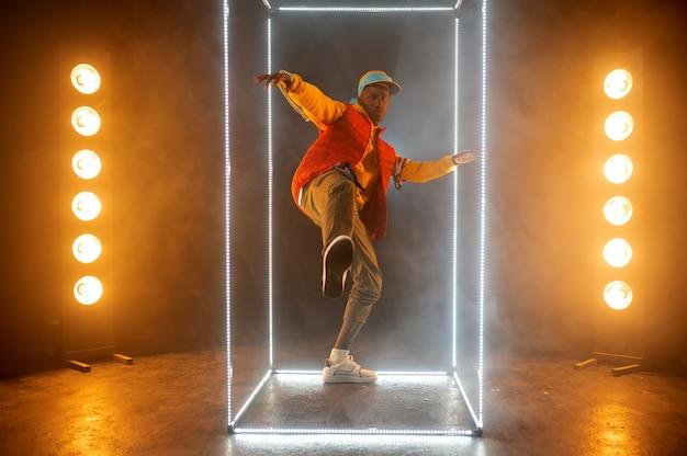 照らされた立方体のステージ上のスタイリッシュなラッパー。ヒップホップパフォーマー、ラップシンガー、ブレイクダンスパフォーマンス、エンターテインメントライフスタイル