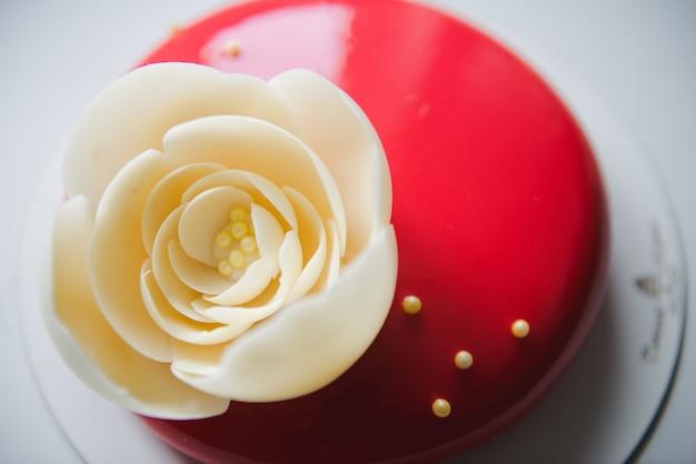 白いバラとスタイリッシュな赤いケーキ。ホワイトチョコレートの大きな花が付いた赤いケーキ。誕生日ケーキ