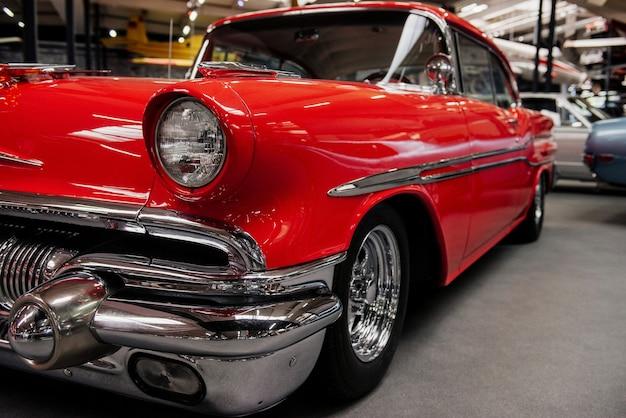 車両展示会に立つレトロコレクションのスタイリッシュな赤い車