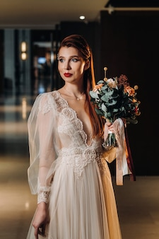 Stylish red-haired bride in a dress with sleeves and a bouquet in the interior