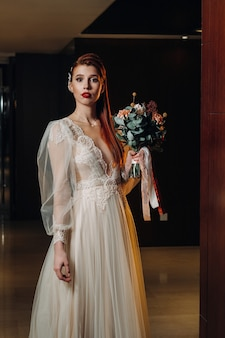 Стильная рыжеволосая невеста в платье с рукавами и букетом в интерьере.