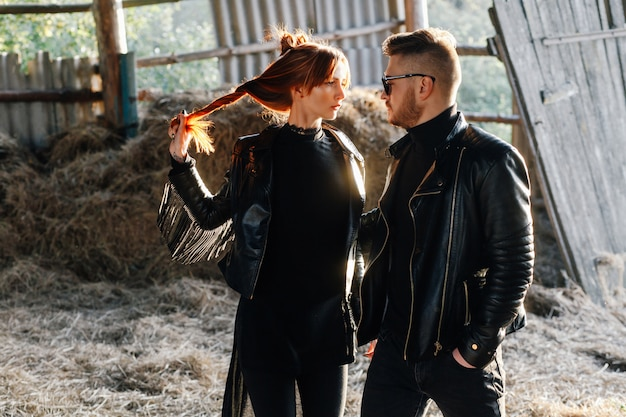 Stylish red-haired girl is standing with her bearded guy and looking at him holding on to her hair