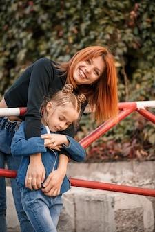 Стильная рыжеволосая мама и дочка тепло разговаривают. счастливый ребенок и ее мама на улице. успешная мать-одиночка с дочерью на прогулке. теплые семейные отношения