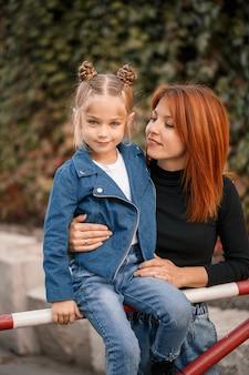 スタイリッシュな赤髪の母と娘が温かく話している。幸せな子供と路上で彼女のお母さん。散歩のために彼女の娘と一緒に成功した独身の母親。暖かい家族関係