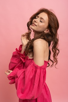 Stylish red-haired woman playing with hairs and posing on pink lien dress with sleeves on pink