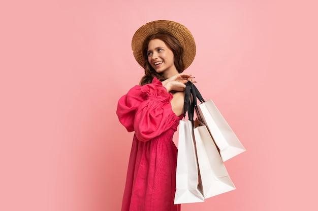 ピンクの壁に袖を付けたピンクのリーン ドレスでポーズをとる白い買い物袋を持つスタイリッシュな赤毛の女性。
