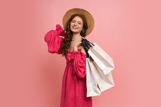 Stylish red-haired woman with white shopping bags posing in pink lien dress with sleeves over pink wall.