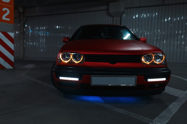 Stylish red old car with new tuning and led headlights in the parking lot at night