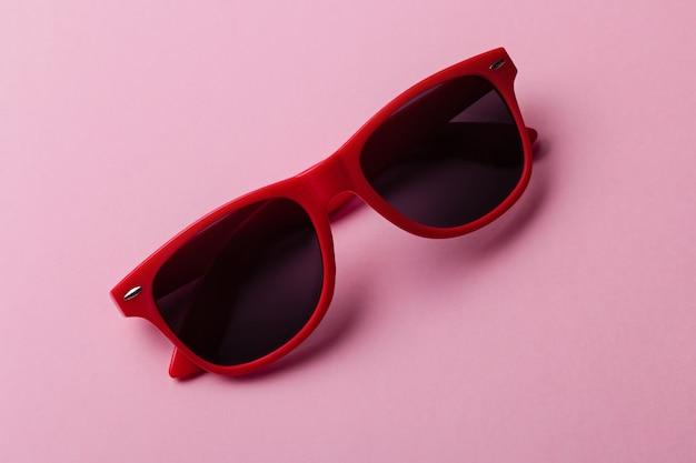 Стильные красные очки крупным планом на розовом фоне