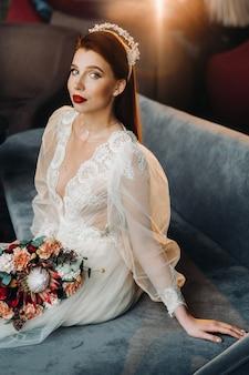 Стильная рыжая невеста в платье с рукавами и букетом в интерьере