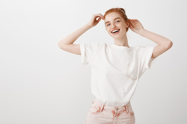 Stylish redhead girl fixing haircut and smiling broadly