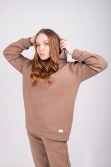 Стильная рыжая девушка в серо-коричневом худи и брюках