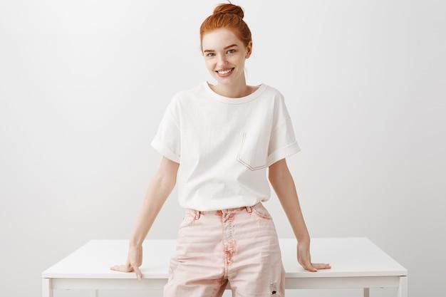 テーブルと白い壁の上に立って無駄のないスタイリッシュな赤毛の女の子