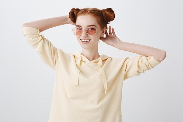 Elegante ragazza adolescente rossa in occhiali da sole che fissano il taglio di capelli