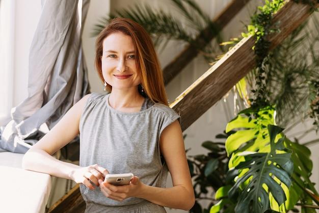 スタイリッシュな赤毛の女性は、植物のある窓辺のそばに立って、電話を持っています Premium写真