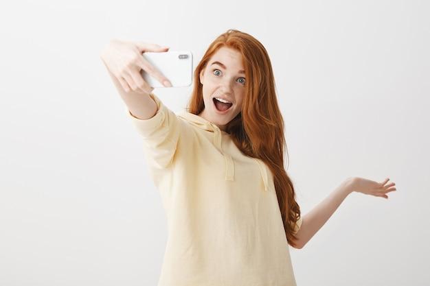 세련 된 빨간 머리 여자 selfie를 복용 하 고 뭔가 보여주는