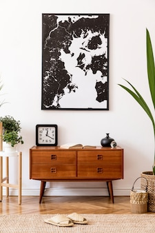 Stylish and retro composition of living room with design wooden retro commode, clock, a lot of plants and elegant accessories. modern home decor. template. mock up poster frame on the wall.