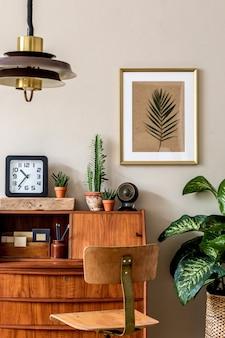 ヴィンテージの木製キャビネット、椅子、植物、時計、ペンダントランプ、エレガントなアクセサリーを備えたホームオフィスインテリアのスタイリッシュなレトロな構成。ゴールドのモックアップポスターフレーム。レトロな家の装飾。