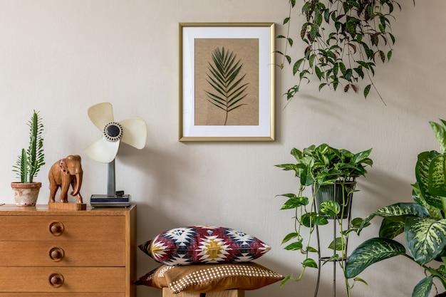 ゴールドのモックアップポスターフレーム、デザイン家具、たくさんの植物、枕、レトロなファン、エレガントなパーソナルアクセサリーを備えたリビングルームのスタイリッシュなレトロなホームステージング。ヴィンテージの家の装飾。レンプレート。