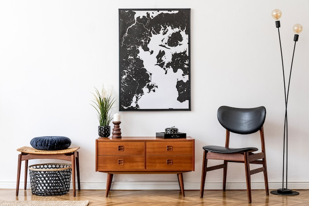 Stylish and retro living room with design vintage wooden commode, chair, footrest, black lamp and elegant personal accessories. map on the wall. vintage home decor.
