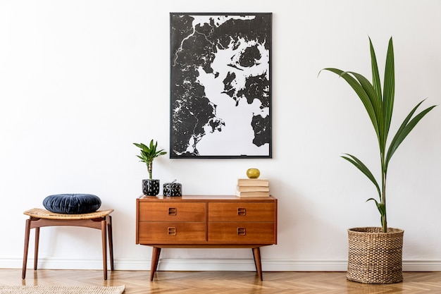 Stylish and retro living room with design vintage wooden commode, footrest, tropical plants, books and elegant personal accessories. map on the wall. home decor.