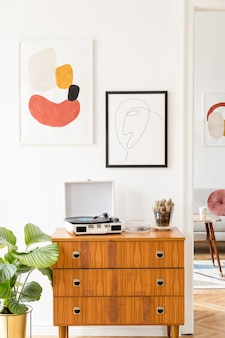 ヴィンテージの箪笥、ポスターフレーム、植物、装飾、エレガントなパーソナルアクセサリーを備えたスタイリッシュなレトロなリビングルーム