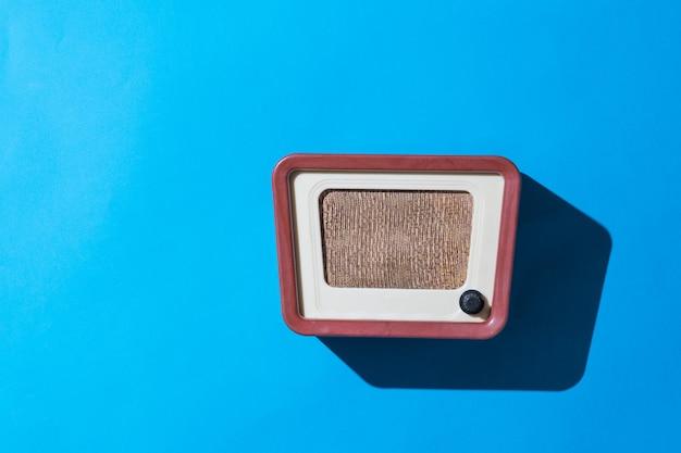 파란색 벽에 세련된 복고풍 라디오. 라디오 방송 라이브. 빈티지 기법.