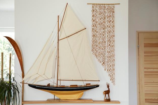 Стильный ретро корабль на деревянной полке в интерьере гостиной