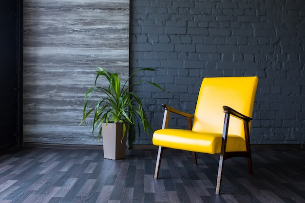 Stylish retro yellow chair in the gray room. brick gray wall. room.