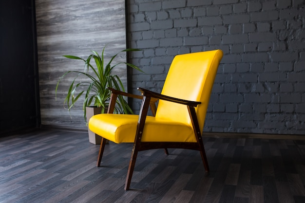 Stylish retro yellow chair in the gray room, brick gray wall,