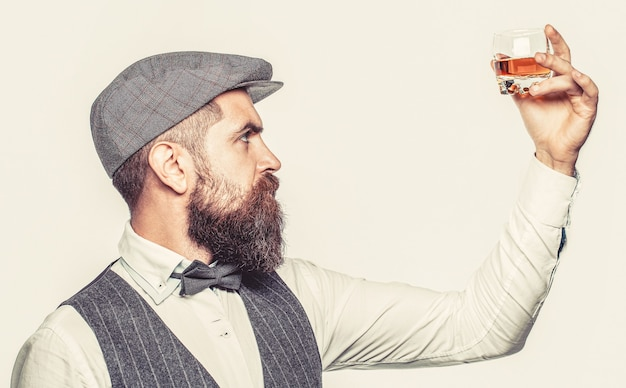 古いウイスキーのグラスを持っているスタイリッシュな金持ち。ひげを生やした紳士はコニャックを飲みます。最高級のウイスキーを飲みます。厚いひげを持つ男の肖像画。マッチョな飲酒。