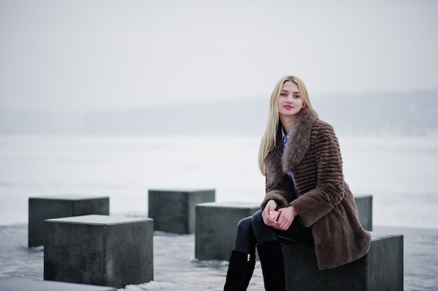 Stylish rich young blonde woman on fur coat with pink smartphone on hand, stone cubes against frozen lake on winter day.