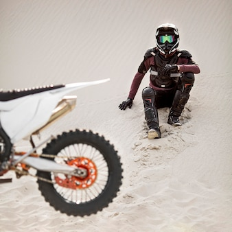 Stylish rider with motorbike in the desert