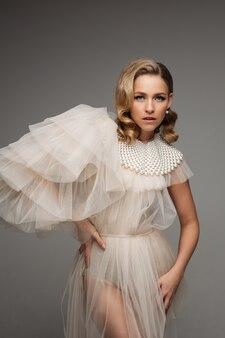 真珠の襟と灰色のスタジオでポーズをとる完璧な髪型のドレスでスタイリッシュなロマンチックな若い美しい女性。