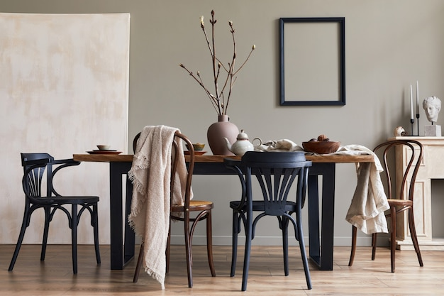 Stylish rustic interior of dining room with walnut wooden table, retro chairs, decoration, fireplace, dried flower, candlestick picture frame and carpet in minimalist home decor..
