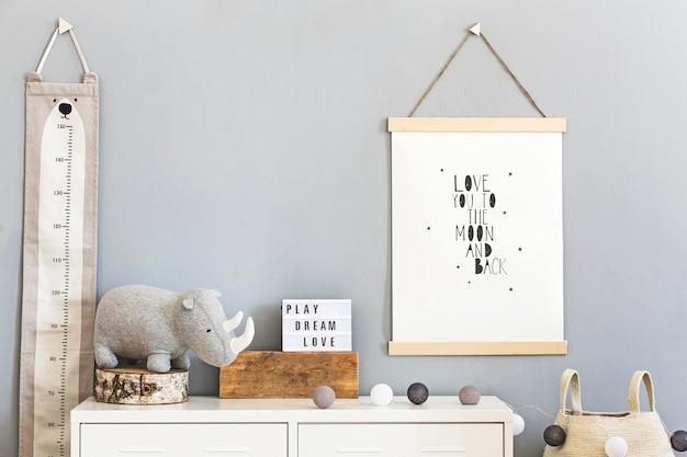 木製のモックアップフォトフレーム、木製とぬいぐるみ、ボックス、ブロック、アクセサリーを備えたスタイリッシュなスカンジチャイルドルーム。背景の壁に星のパターン。明るく日当たりの良いインテリア。室内装飾。