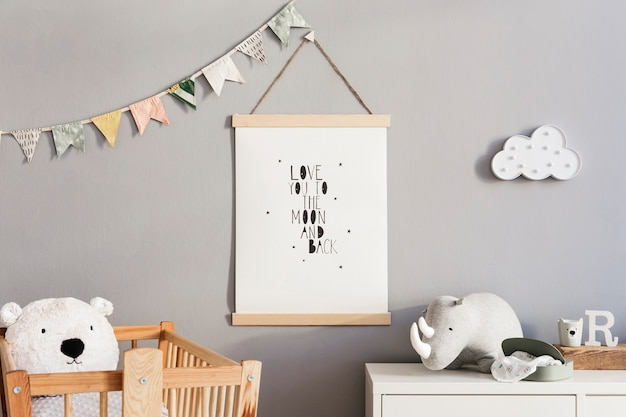 Stylish scandi childroom with wooden mock up photo frame, wooden and plush toys, boxes, blocks and accessories. stars pattern on the background wall. bright and sunny interior. home decor.