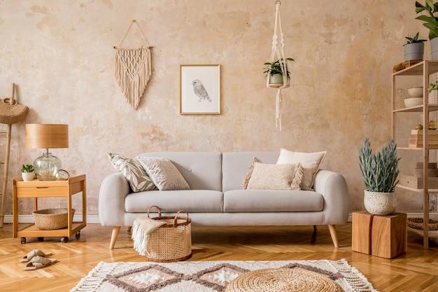 リビング ルームのインテリアにスタイリッシュなスカンディ コンポジションを配置し、グレーのソファ、木製のコーヒー テーブル、棚、立方体、カーペット、籐のプーフ、植物、額縁、テーブル ランプ、エレガントなアクセサリーを家の装飾に使用します。